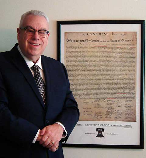 Frank DeFreitas stands next to his re-creation of the Declaration of Independence. The phrases referencing God have been highlighted.