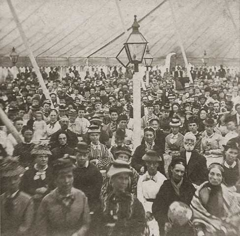 In this photo people assemble under a tent to hear an evangelist on Martha's Vineyard (USA) in the 1800's.